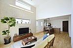 リビング上部の高窓から日差しが降り注ぎ、家族の憩いの場を包み込みます。