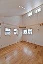 勾配天井のハイサイドライトで明るく広々とした主寝室。