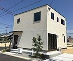 フラット屋根のシンプルなシルエットに外壁は手作り感のあるこだわりのデザインです。