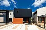 【施工事例:黒ガルバの家/白い三角屋根の家】 ガルバリウム鋼板ならではのスタイリッシュな光沢感とウッドデッキのブラウンが色鮮やか。総2階の三角屋根は外観がコンパクトに見えてナチュラルかわいい印象に。
