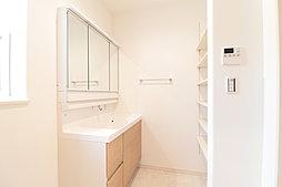 ワイドな洗面台の後ろはたっぷり入る可動棚