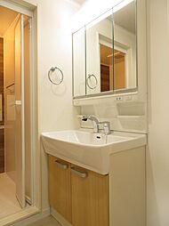 扱いやすいシャワー付き水栓。ミラーの裏側すべてが収納スペースで、広い鏡面を使える3面鏡タイプの洗面化粧台です。浴室と雰囲気を合わせた洗面台が素敵です。(2019年7月20日撮影)