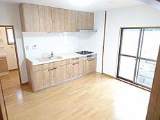 リフォーム済写真キッチンは新品のシステムキッチンに新品交換しました。天井・壁クロスの張り替え、床の重ね張りを行いました。新しいキッチンだと家事が楽しみに変わりそうですね。