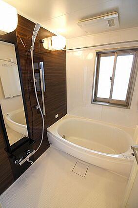 広い浴槽と窓付...